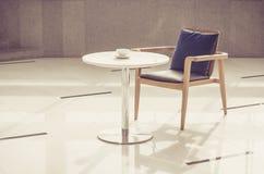 Lehnsessel und Tabelle mit Kaffeetasse Lizenzfreie Stockfotografie