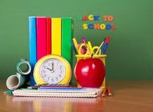 Lehrbücher, Bleistifte, Griffe und Apfel Stockbild