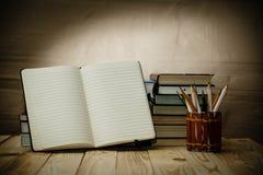 Lehrbücher und Bücher auf einem Holztisch Stockfoto