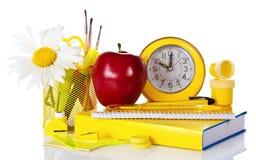 Lehrbuch mit einer Uhr und einem roten Apfel Stockfotografie
