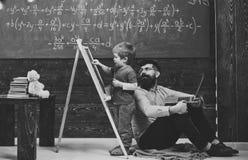 Lehrer überprüft Studentenschreiben auf Tafel Schüler, der mit seinem Tutor oder Vati beim Lösen der Aufgabe spricht Schöne fälli lizenzfreie stockfotos