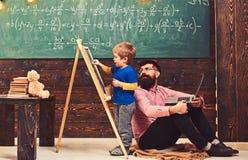 Lehrer überprüft Studentenschreiben auf Tafel Schüler, der mit seinem Tutor oder Vati beim Lösen der Aufgabe spricht Schöne fälli lizenzfreie stockbilder
