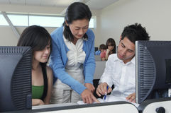 Lehrer-Assisting Students In-Computer-Labor Stockfoto