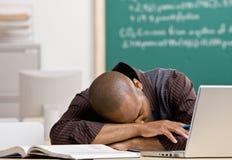 Lehrer, der auf Schreibtisch im Schuleklassenzimmer legt Lizenzfreie Stockbilder