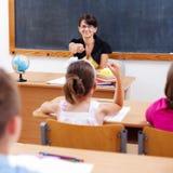 Lehrer, der auf Schulmädchen zeigt Stockfotos