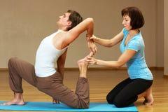 Lehrer, der bei der Yogahaltung hilft lizenzfreies stockbild