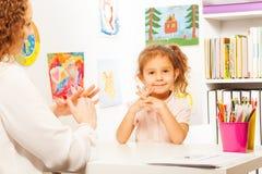 Lehrer, der bei Tisch Fingerübungen zum Schüler zeigt Stockbilder
