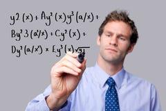Lehrer, der eine Mathegleichung schreibt. Lizenzfreies Stockfoto