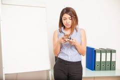 Lehrer, der einen Smartphone im Klassenzimmer verwendet Stockbilder