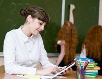 Lehrer, der einen Tablet-Computer am Klassenzimmer hält Stockfotografie