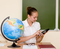 Lehrer, der einen Tablet-Computer am Klassenzimmer verwendet Lizenzfreie Stockfotografie