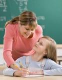 Lehrer, der Heimarbeit Kursteilnehmer erklärt Lizenzfreie Stockbilder