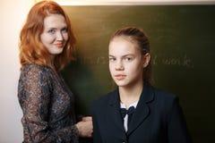 Lehrer, der ihren Studenten eine Frage an der Volksschule stellt stockfotografie