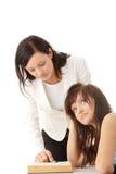 Lehrer, der jugendlich Kursteilnehmer hilft Stockbilder