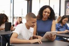 Lehrer, der Jugendschüler mit Tablet-Computer hilft stockbilder