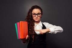 Lehrer der jungen Frau in den Gläsern zeigend auf Stapel der Bücher Stockfotografie