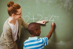 Lehrer, der Jungen unterstützt, um auf Tafel in Klassenzimmer zu schreiben Stockbilder