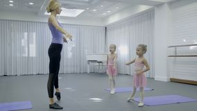 Lehrer der Kind-` s Tanzschule zeigt Mädchen Übungen im Studio stock footage
