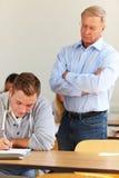 Lehrer, der Kursteilnehmer an der Prüfung überprüft Lizenzfreie Stockfotos