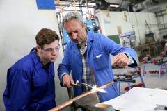 Lehrer, der Lehrling metallurgische Techniken zeigt Stockfotografie