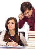 Lehrer, der nahe bei dem Studenten untersucht seine Hausarbeit steht Stockfoto