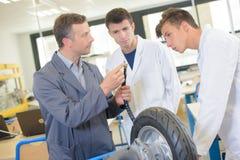 Lehrer, der Studenten Adapter für das Aufblasen des Reifens zeigt Stockfoto