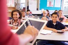 Lehrer, der Tablet-Computer in der Volksschulelektion verwendet Lizenzfreie Stockfotografie