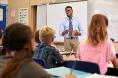 Lehrer, der Tablet-Computer in einer grundlegenden Schulklasse verwendet lizenzfreie stockbilder