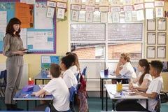 Lehrer, der Tablet-Computer während einer Grundschuleklasse verwendet lizenzfreie stockbilder