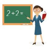 Lehrer an der Tafel mit einem Lehrbuch Stockfoto