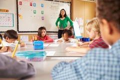 Lehrer, der Volksschulekinder im Klassenzimmer anweist Stockfotos