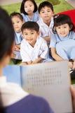 Lehrer, der zu den Kursteilnehmern auf Chinesen liest lizenzfreie stockbilder