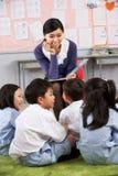 Lehrer, der zu den Kursteilnehmern in der chinesischen Schule liest Stockbilder