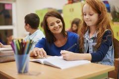 Lehrer, der zu ihrem Schüler hilft Stockfoto