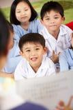 Lehrer, der zum Kursteilnehmer-Schule-Klassenzimmer liest stockfotos