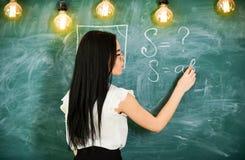 Lehrer des Mathematikschreibens auf Tafel, hintere Ansicht Sexy Lehrerkonzept Sexy Lehrer Dame beim Glaserklären Lizenzfreies Stockfoto