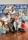 Lehrer, die Gitarre mit Pupillen spielen Lizenzfreie Stockbilder