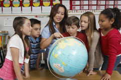 Lehrer-Explaining Globe To-Studenten Lizenzfreie Stockfotos