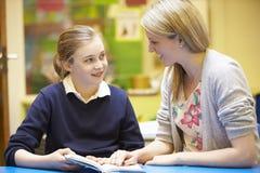 Lehrer-With Female Pupil-Lesung am Schreibtisch im Klassenzimmer Stockbilder