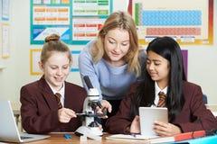 Lehrer With Female Students, das Mikroskop in der Wissenschafts-Klasse verwendet lizenzfreies stockfoto
