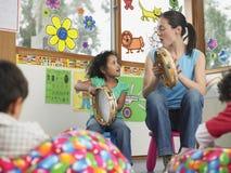 Lehrer-With Girl Playing-Musik in der Klasse lizenzfreie stockfotos
