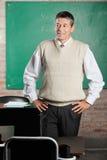 Lehrer-With Hands On-Hüften, die weg herein schauen lizenzfreie stockfotografie