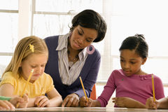Lehrer-helfende Kursteilnehmer mit Schoolwork lizenzfreie stockfotografie