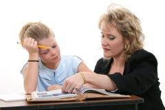 Lehrer-helfender Kursteilnehmer am Schreibtisch Lizenzfreie Stockbilder