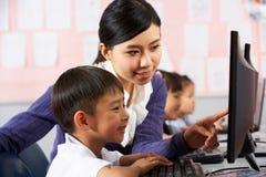 Lehrer-helfender Kursteilnehmer während der Computer-Kategorie Stockfotos