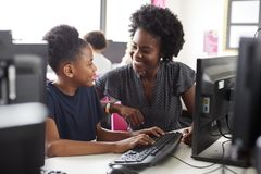 Lehrer-Helping Female High-Schüler Working am Schirm in der Computer-Klasse lizenzfreie stockfotos