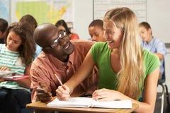 Lehrer Helping Female Pupil, das am Schreibtisch im Klassenzimmer studiert Lizenzfreies Stockbild