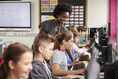 Lehrer-Helping Female Pupil-Linie von den hohen Schülern, die an den Schirmen in der Computer-Klasse arbeiten lizenzfreies stockbild