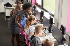 Lehrer-Helping Female Pupil-Linie von den hohen Schülern, die an den Schirmen in der Computer-Klasse arbeiten stockbild
