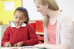 Lehrer Helping Female Pupil mit dem übenden Ablesen am Schreibtisch Stockbild